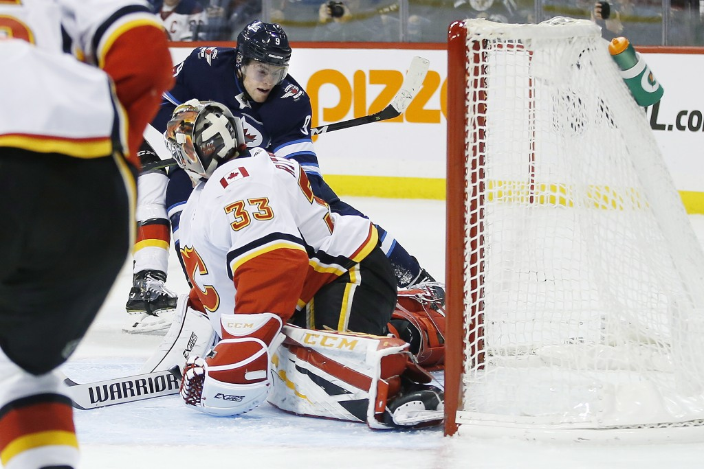 Winnipeg Jets' Andrew Copp's (9) shot is saved by Calgary Flames goaltender David Rittich (33) during second-period NHL hockey game action in Winnipeg...