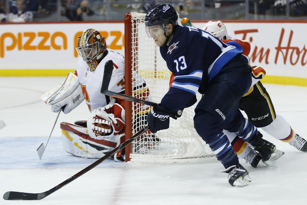 Winnipeg Jets' Brandon Tanev (13) attempts a wraparound against Calgary Flames goaltender David Rittich (33) during second-period NHL hockey game acti...