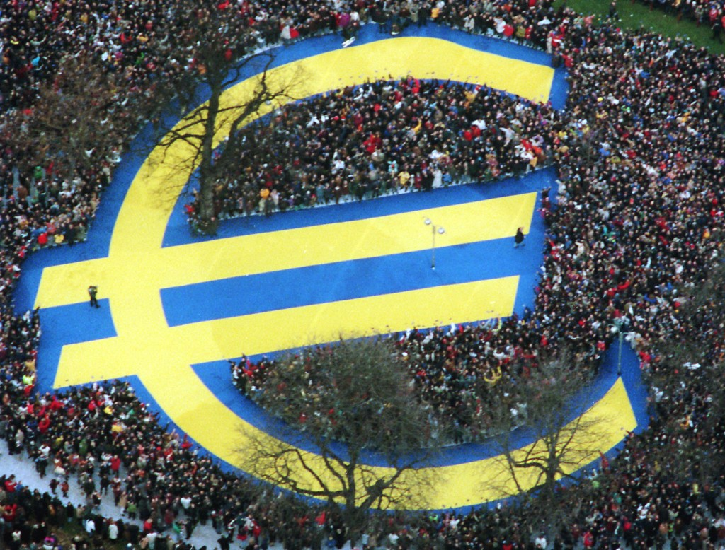 FILE  - In this Friday, Jan. 1, 1999 file photo, thousands of people stand around a huge Euro symbol displayed in a park in Frankfurt's banking distri...