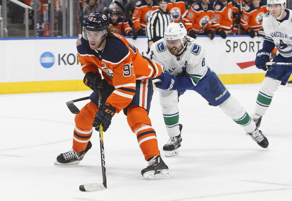 Vancouver Canucks' Chris Tanev (8) chases Edmonton Oilers' Connor McDavid (97) during the second period of an NHL hockey game Thursday, Dec. 27, 2018,...