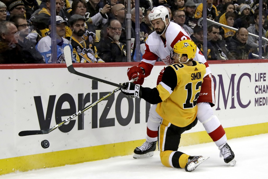 Pittsburgh Penguins' Dominik Simon (12) is checked off the puck by Detroit Red Wings' Jonathan Ericsson (52) during the second period of an NHL hockey