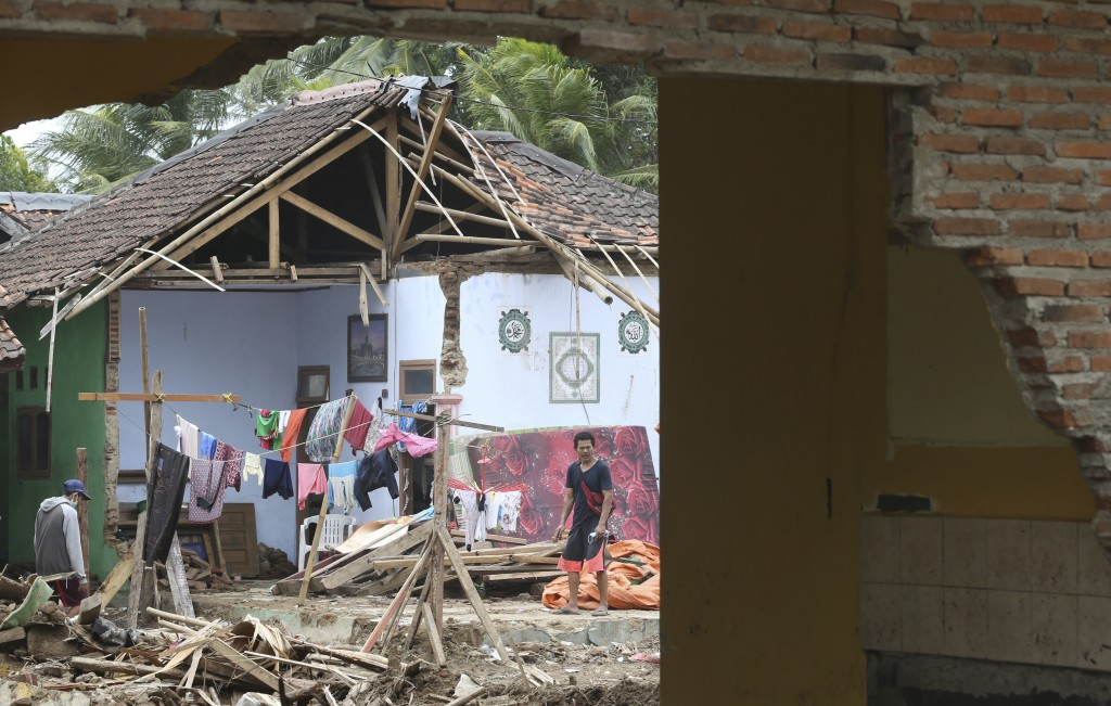A man removes debris from his damaged home in the tsunami-hit village of Carita, Indonesia, Friday, Dec. 28, 2018. Indonesia has widened the no-go zon