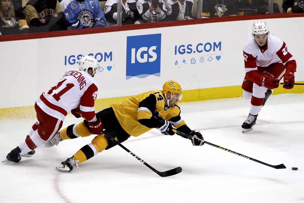 Pittsburgh Penguins' Tanner Pearson (14) gets off a pass as he falls to the ice with Detroit Red Wings' Luke Glendening (41) defending during the firs