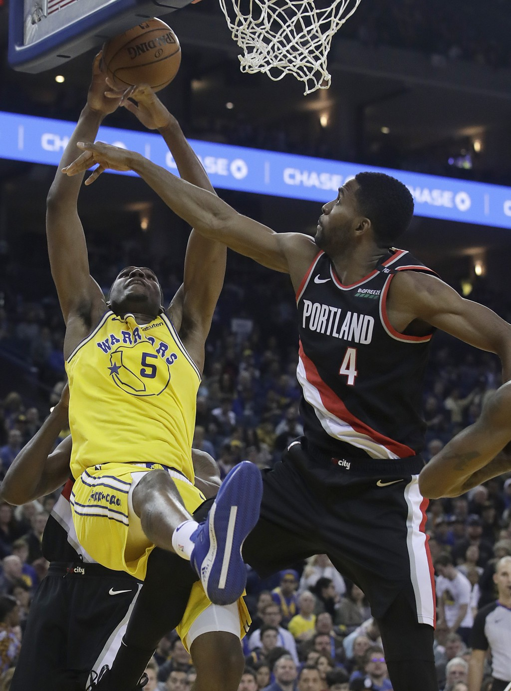 Golden State Warriors forward Kevon Looney (5) reaches for the ball next to Portland Trail Blazers forward Maurice Harkless (4) during the first half ...