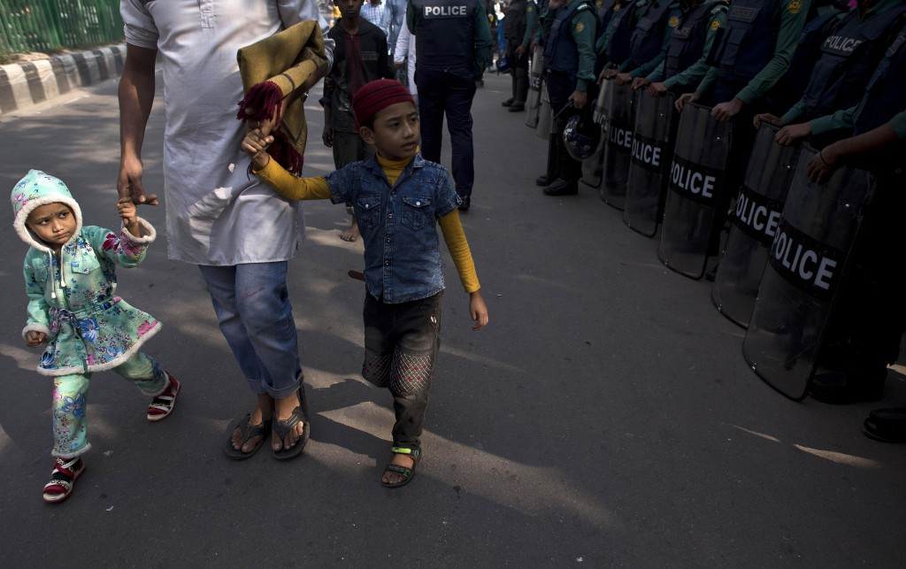 Bangladeshi Muslim children walk along with their father after attending the Friday prayers at a mosque ahead of the general elections in Dhaka, Bangl...