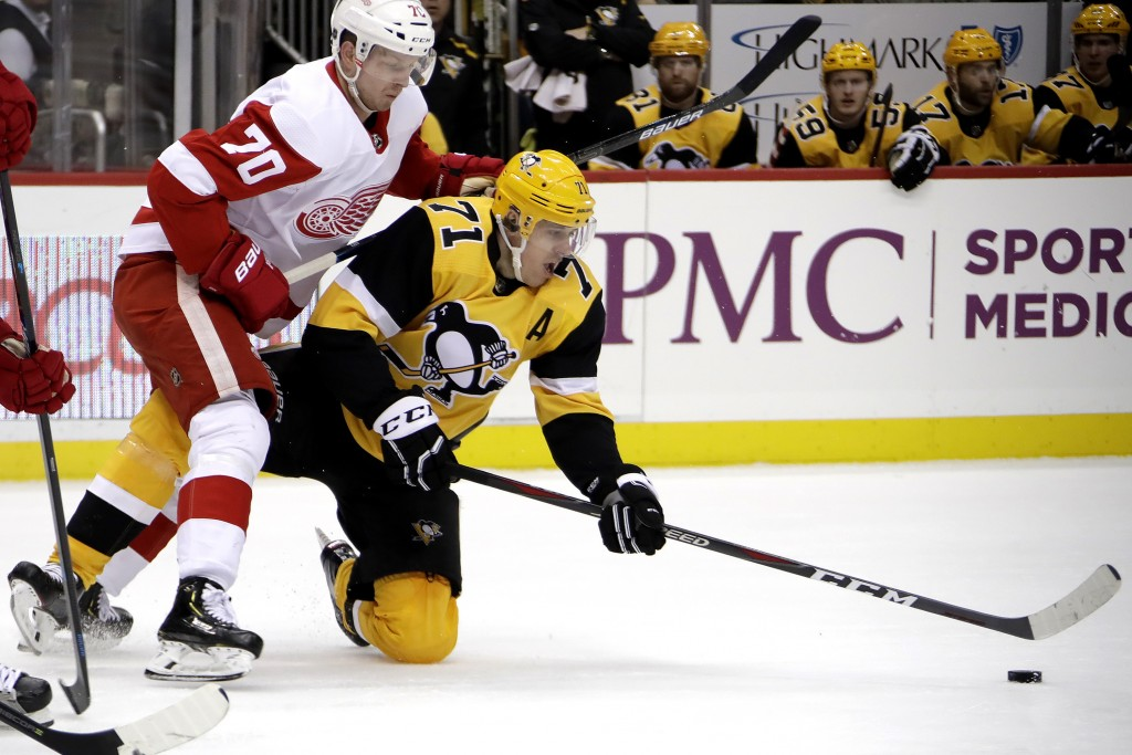 Pittsburgh Penguins' Evgeni Malkin (71) gets off a pass as he falls to the ice with Detroit Red Wings' Christoffer Ehn (70) defending during the secon...