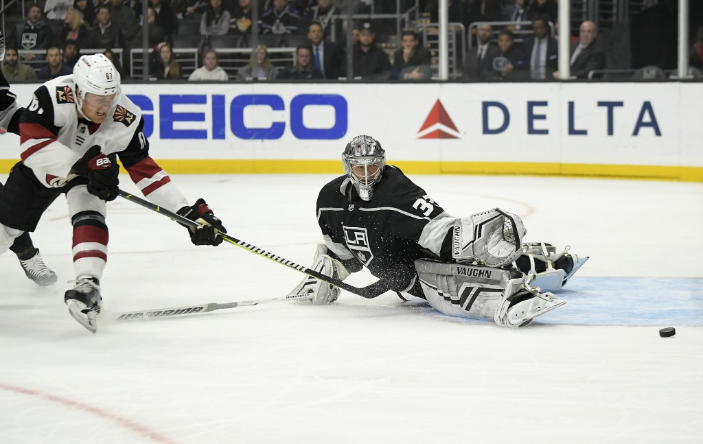 Los Angeles Kings goaltender Jonathan Quick, right, deflects a shot by Arizona Coyotes left wing Lawson Crouse during the first period of an NHL hocke...
