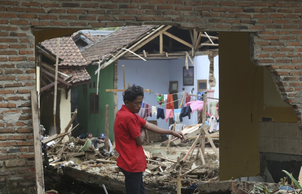 A man views the destruction to his home in the tsunami-hit village of Carita, Indonesia, Friday, Dec. 28, 2018. Indonesia has widened the no-go zone a...
