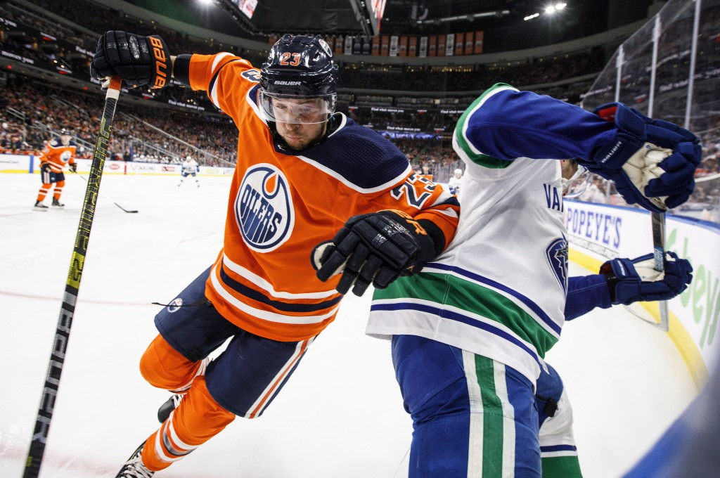 Vancouver Canucks' Bo Horvat (53) is checked by Edmonton Oilers' Ryan Spooner, left, during the first period of an NHL hockey game Thursday, Dec. 27, ...
