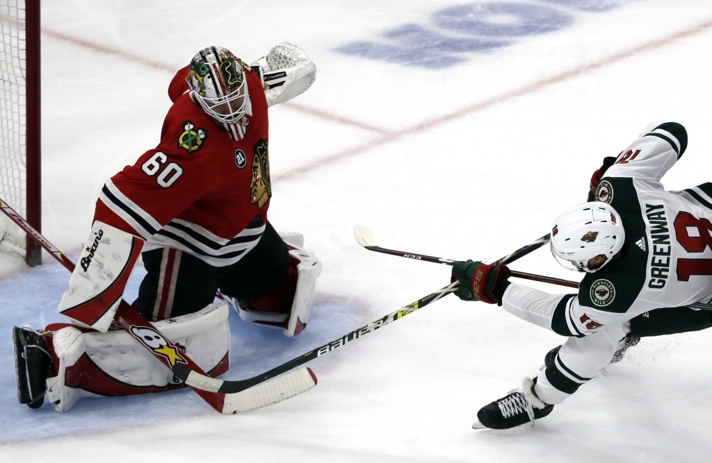 Chicago Blackhawks goalie Collin Delia, left, blocks a shot by Minnesota Wild left wing Jordan Greenway during the second period of an NHL hockey game...