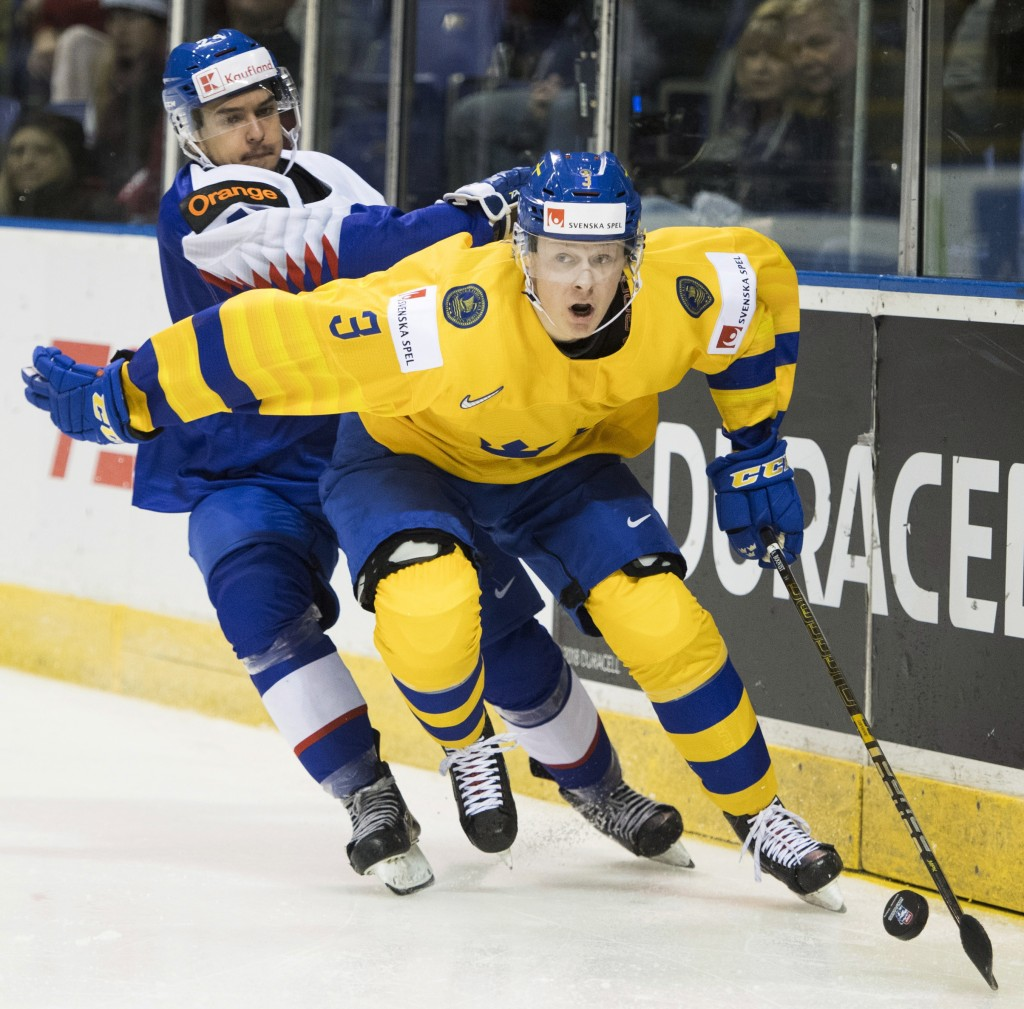 Sweden's Adam Boqvist (3) fights for control of the puck with Slovakia's Jozef Balaz (24) during the second period of a world junior hockey championsh