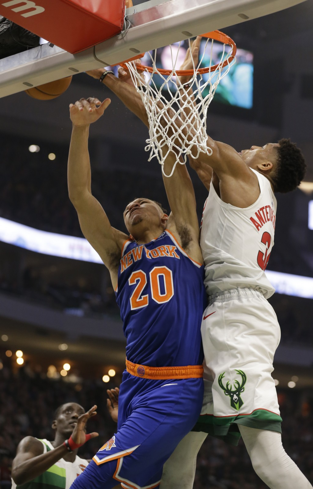Milwaukee Bucks' Giannis Antetokounmpo, right, blocks the shot by New York Knicks' Kevin Knox during the first half of an NBA basketball game Thursday...