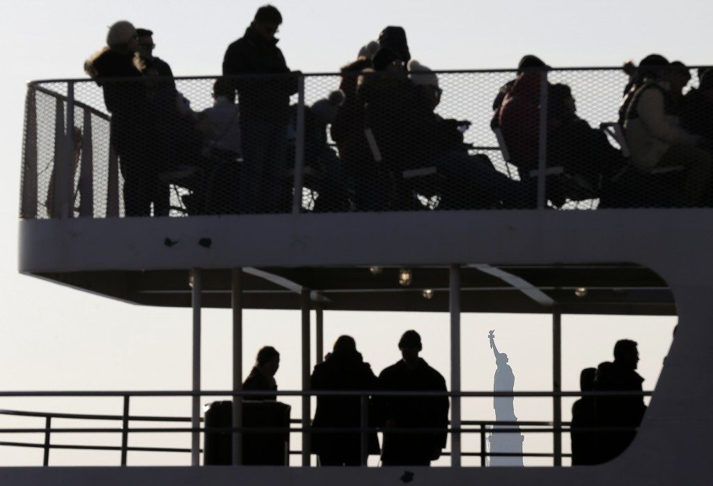 Tourists board a boat headed for the Statue of Liberty in New York, Thursday, Dec. 27, 2018. The Statue of Liberty and Ellis Island will remain open d...