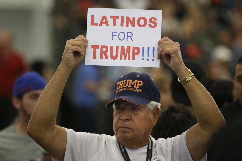 FILE - In this May 25, 2016, file photo, a man holds up a sign for then-Republican presidential candidate Donald Trump before the start of a rally at ...