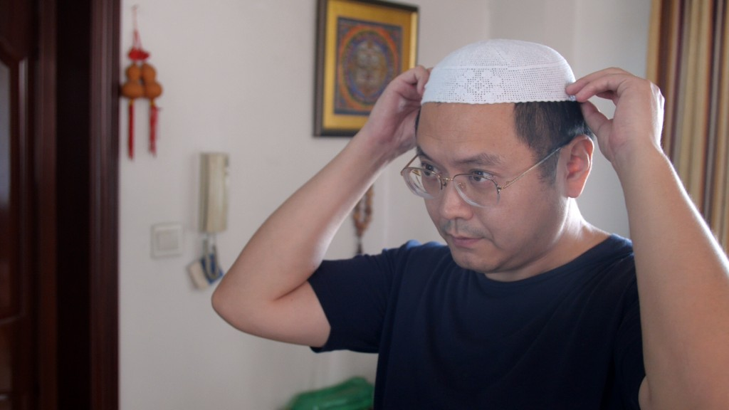 In this Sept. 28, 2018, photo, Muslim Chinese poet Cui Haoxin dons an Islamic hat in his home in the city of Jinan in the eastern province of Shandong