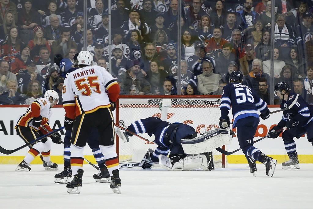 Winnipeg Jets Calgary Flames' Johnny Gaudreau (13) scores against Winnipeg Jets goaltender Connor Hellebuyck (37) during second-period NHL hockey game...