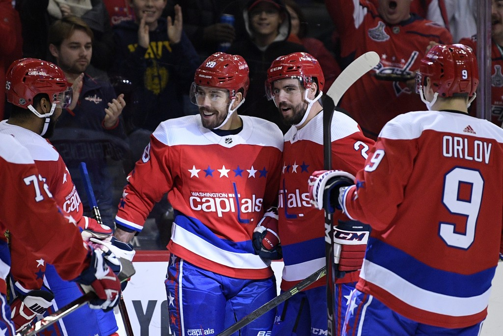 Washington Capitals center Chandler Stephenson (18) celebrates his goal with defenseman Matt Niskanen (2), defenseman Dmitry Orlov (9) and right wing