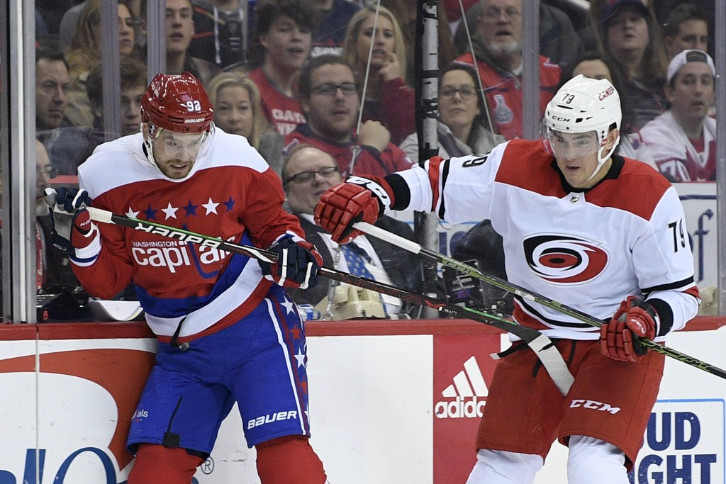 Washington Capitals center Evgeny Kuznetsov (92), of Russia, battles against Carolina Hurricanes left wing Micheal Ferland (79) during the second peri