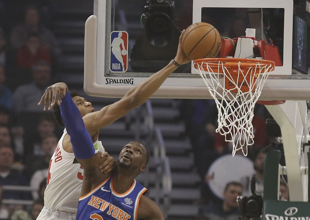Milwaukee Bucks' Giannis Antetokounmpo, left, tries to dunk over New York Knicks' Noah Vonieh during the first half of an NBA basketball game Thursday...