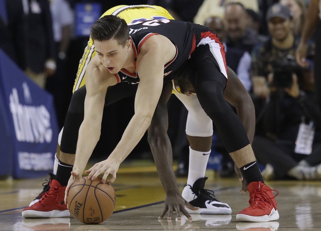 Portland Trail Blazers forward Zach Collins, foreground, reaches for the ball in front of Golden State Warriors forward Draymond Green during the firs...