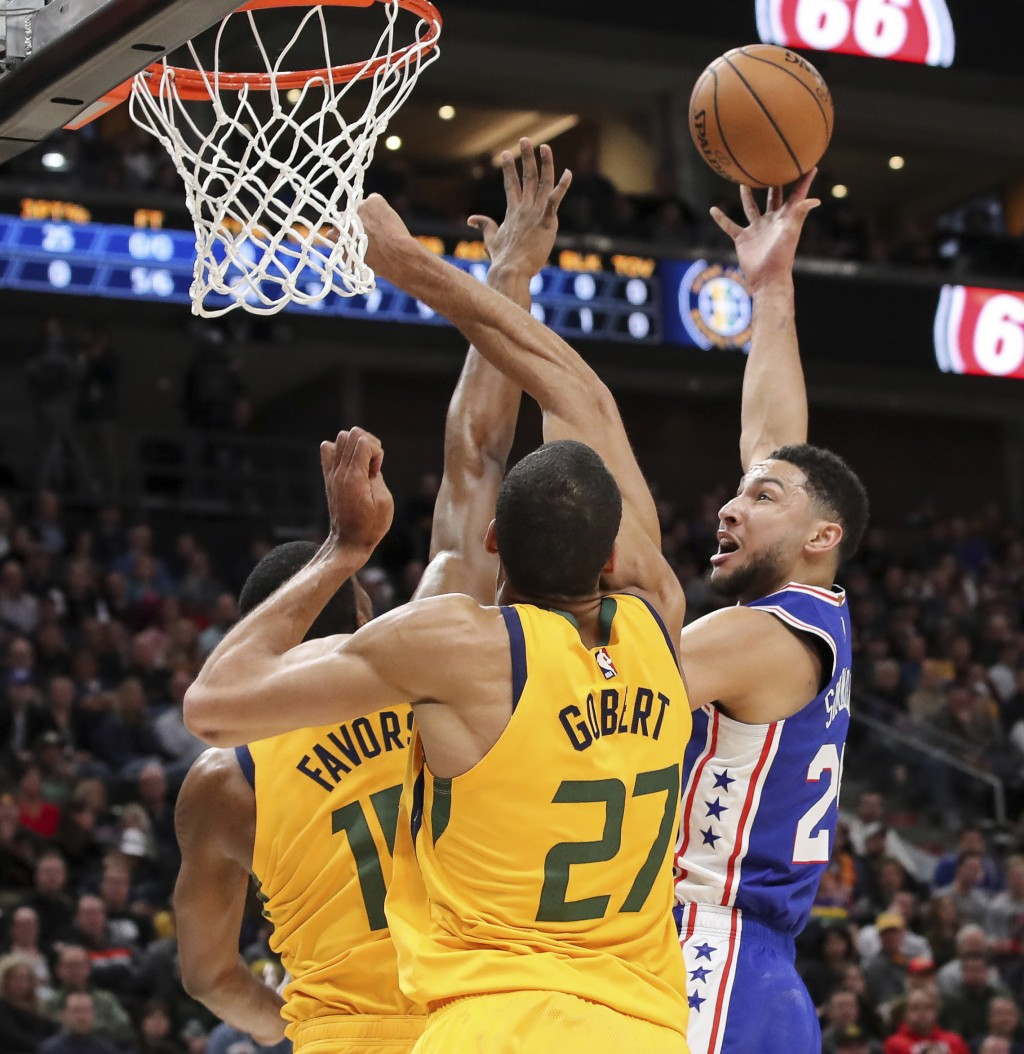 Philadelphia 76ers guard Ben Simmons (25) shoots over Utah Jazz forward Derrick Favors (15) and center Rudy Gobert (27) during the first quarter of an...