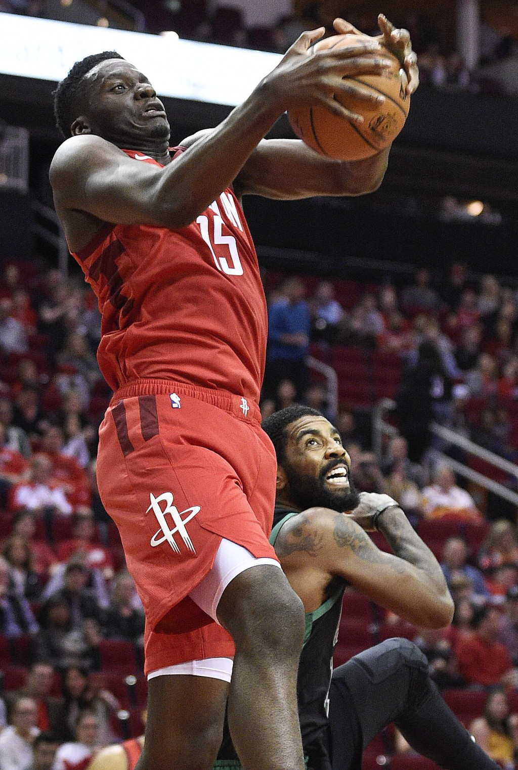 Houston Rockets center Clint Capela, left, grabs a rebound above Boston Celtics guard Kyrie Irving during the first half of an NBA basketball game, Th...