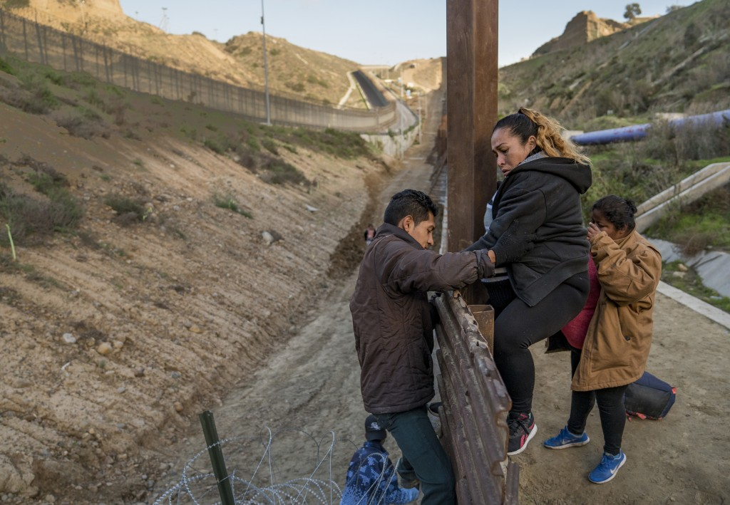 A pregnant migrant climbs the border fence before jumping into the U.S. to San Diego, Calif., from Tijuana, Mexico, Thursday, Dec. 27, 2018. Discourag...