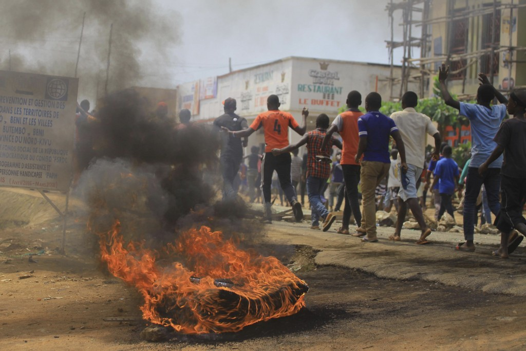 Protesters walk past a burning tyre in the Eastern Congolese town of Beni, Friday Dec. 28, 2018, as they demonstrate against the election postponed un...