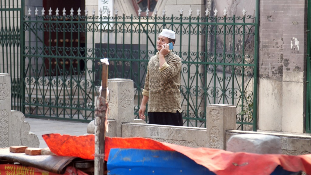 In this Sept. 27, 2018, photo, a Hui Muslim man talks on his mobile phone outside the Nandashi Great Southern Mosque in Jinan in China's eastern provi