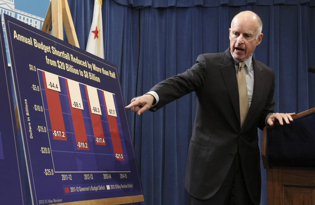 FILE - In this May 14, 2012, file photo, Gov. Jerry Brown points to a chart showing how his budget plans will eventually reduce the budget deficit ove