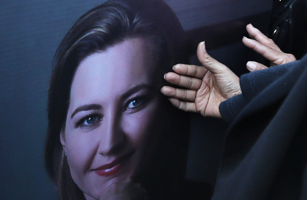 Women touch the a portrait showing Puebla state Gov. Martha Erika Alonso during a farewell ceremony in Puebla, southeast of Mexico City, on Tuesday, D...