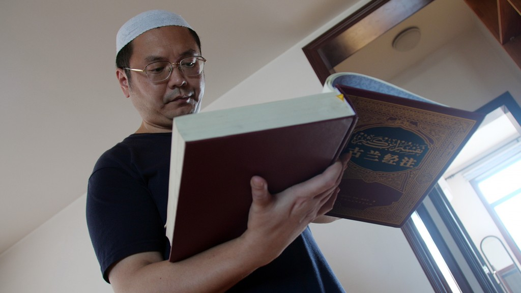 In this Sept. 28, 2018, photo, Muslim Chinese poet Cui Haoxin reads an Arabic prayer from a Quran in his home in the city of Jinan in China's eastern