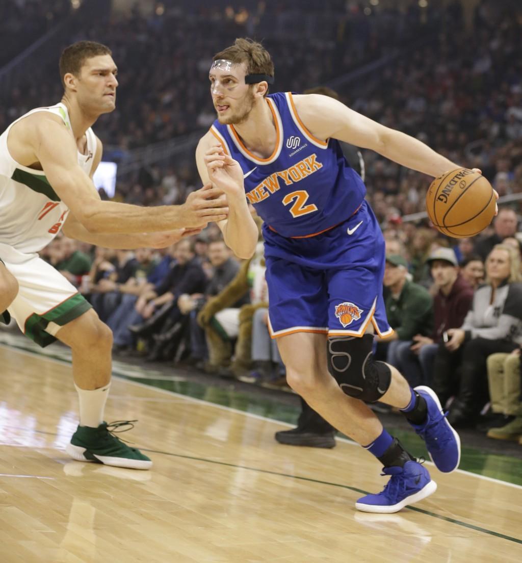 New York Knicks' Luke Kornet (2) drives against Milwaukee Bucks' Brook Lopez during the first half of an NBA basketball game Thursday, Dec. 27, 2018, ...