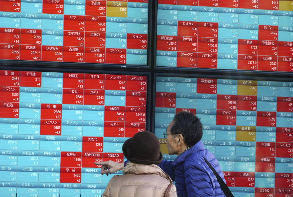 A man and a woman look at an electronic stock board showing Japan's Nikkei 225 index at a securities firm in Tokyo Friday, Dec. 28, 2018. Most Asian s...