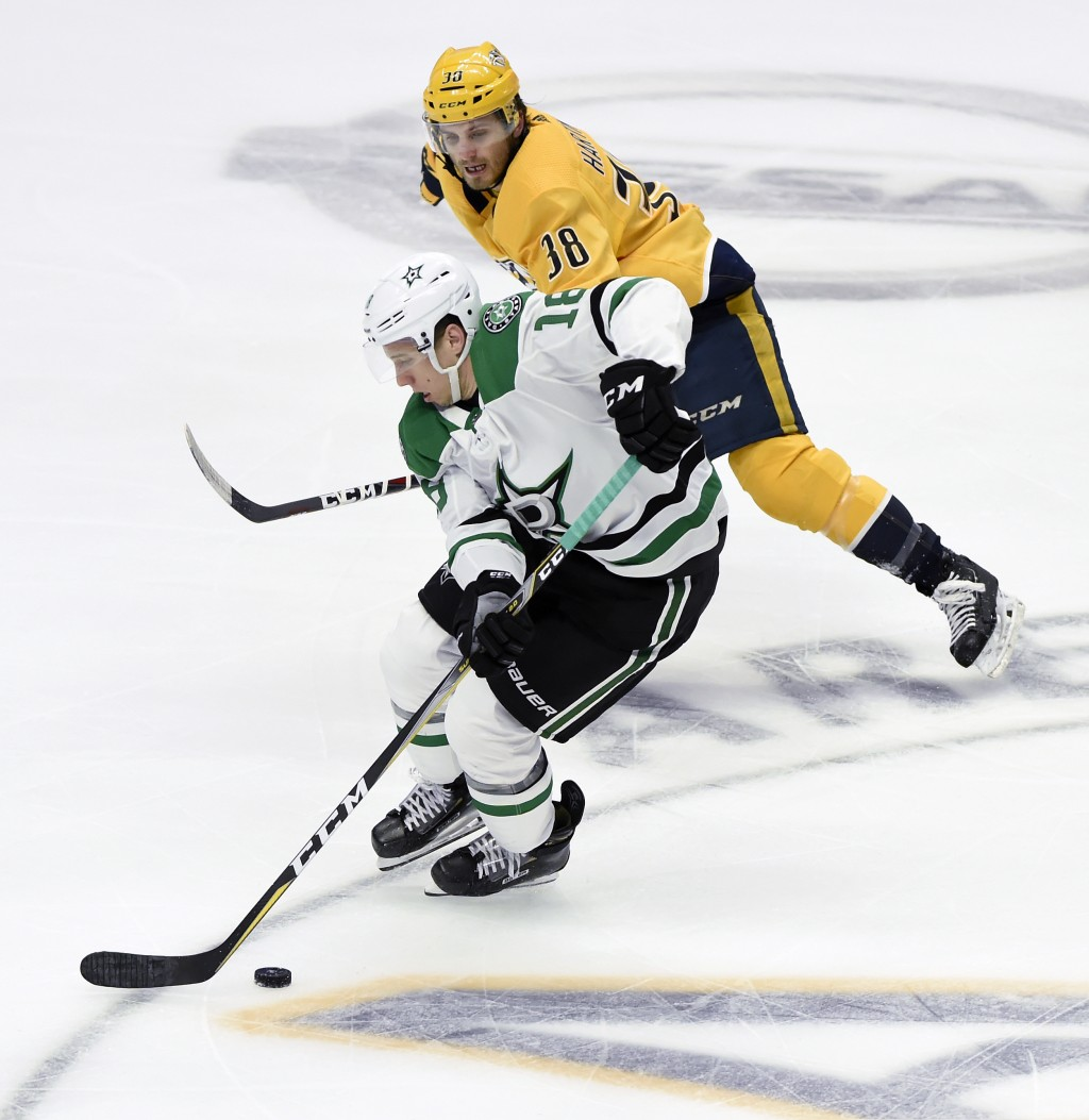 Dallas Stars center Tyler Pitlick (18) moves the puck past Nashville Predators right wing Ryan Hartman (38) during the first period of an NHL hockey g...
