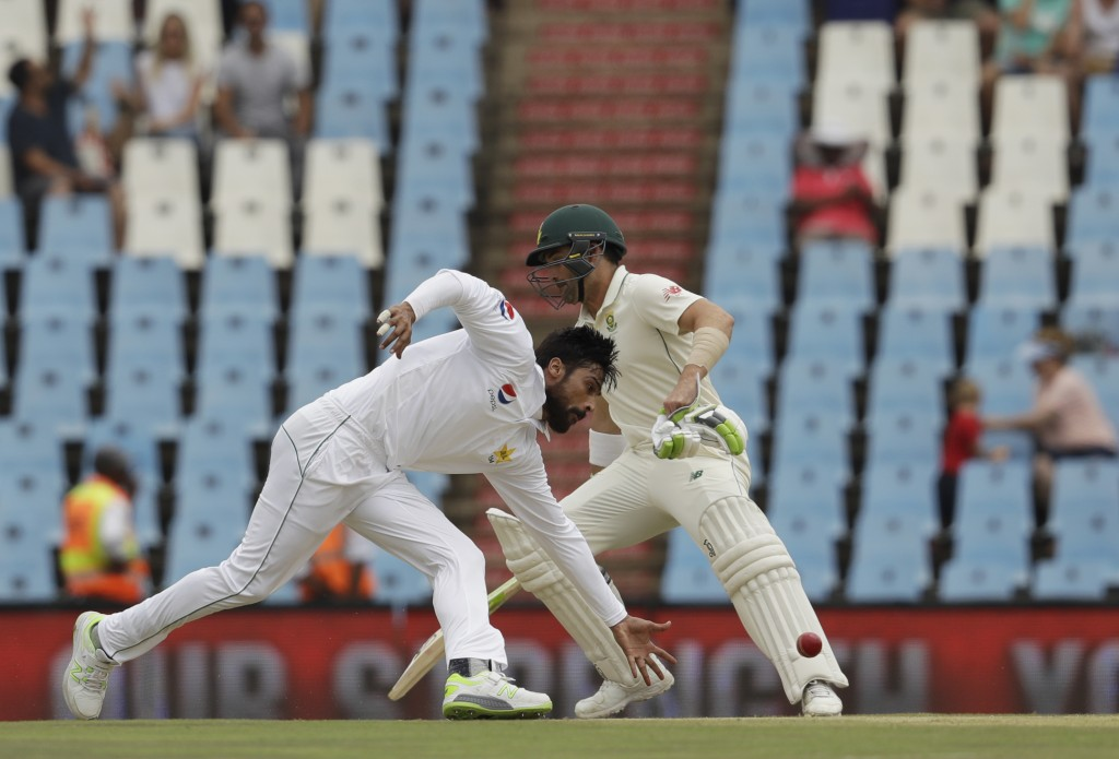 Pakistan's bowler Mohammad Amir, left, field off own bowling as South Africa's batsman Dean Elgar makes a turn on day three of the first cricket test ...