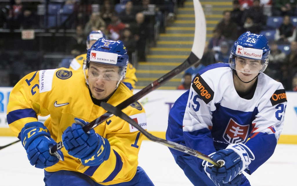 Sweden's Erik Brannstrom (12) fights for control of the puck with Slovakia's Martin Pospisil (25) during the second period of a world junior hockey ch