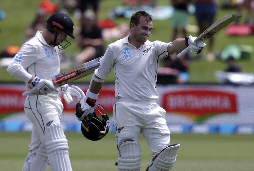 New Zealand's Tom Latham celebrates after reaching his century as teammate Henry Nicholls watches during play on day three of the second cricket test ...