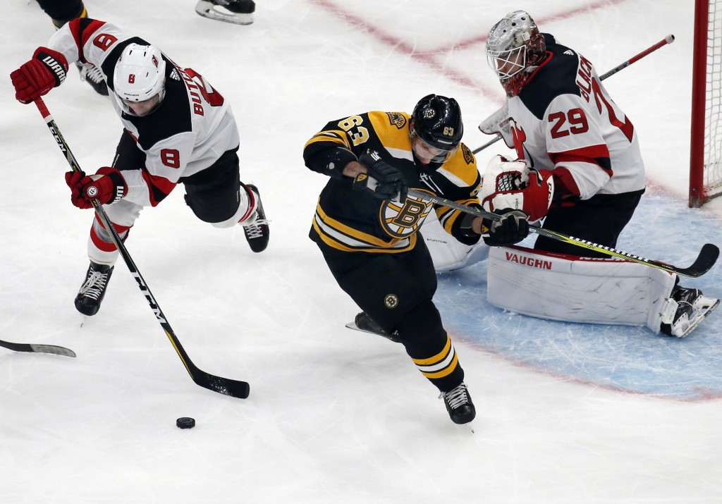 New Jersey Devils defenseman Will Butcher (8) clears the puck away from Boston Bruins left wing Brad Marchand (63) as Devils goaltender Mackenzie Blac...