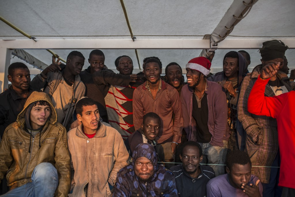Migrants gather on the deck of the Spanish NGO Proactiva Open Arms rescue vessel after being rescued in the central Mediterranean sea Dec. 21, 2018, b...