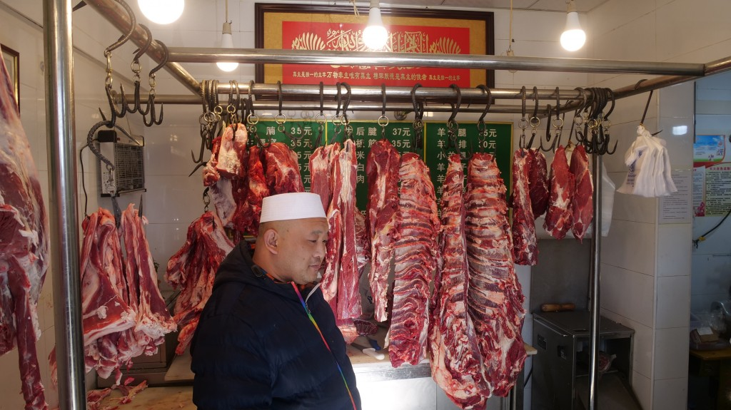 In this Dec. 7, 2018, photo, Ma Changli, 39, stands in the butcher shop that he has run in the Islamic neighborhood of Niujie for 5 years after moving
