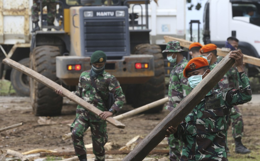 Soldiers remove debris from a damaged house in the tsunami-hit village of Carita, Indonesia, Friday, Dec. 28, 2018. Indonesia has widened the no-go zo