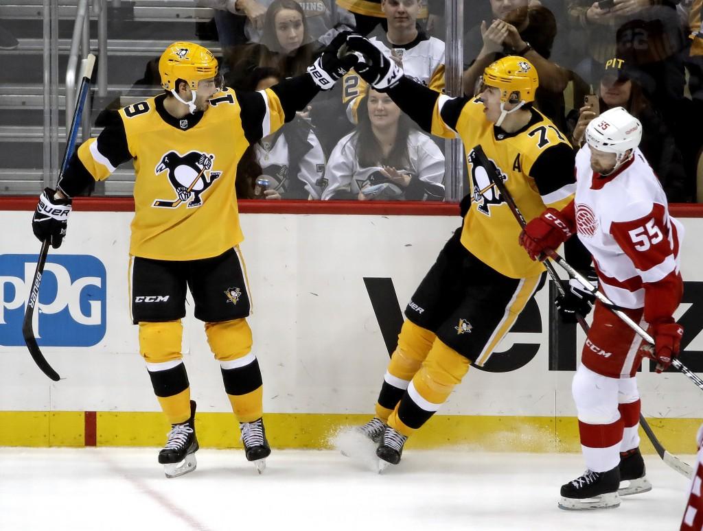 Pittsburgh Penguins' Derick Brassard (19) celebrates his empty-net goal with Evgeni Malkin (71) as Detroit Red Wings' Niklas Kronwall (55) skates back...