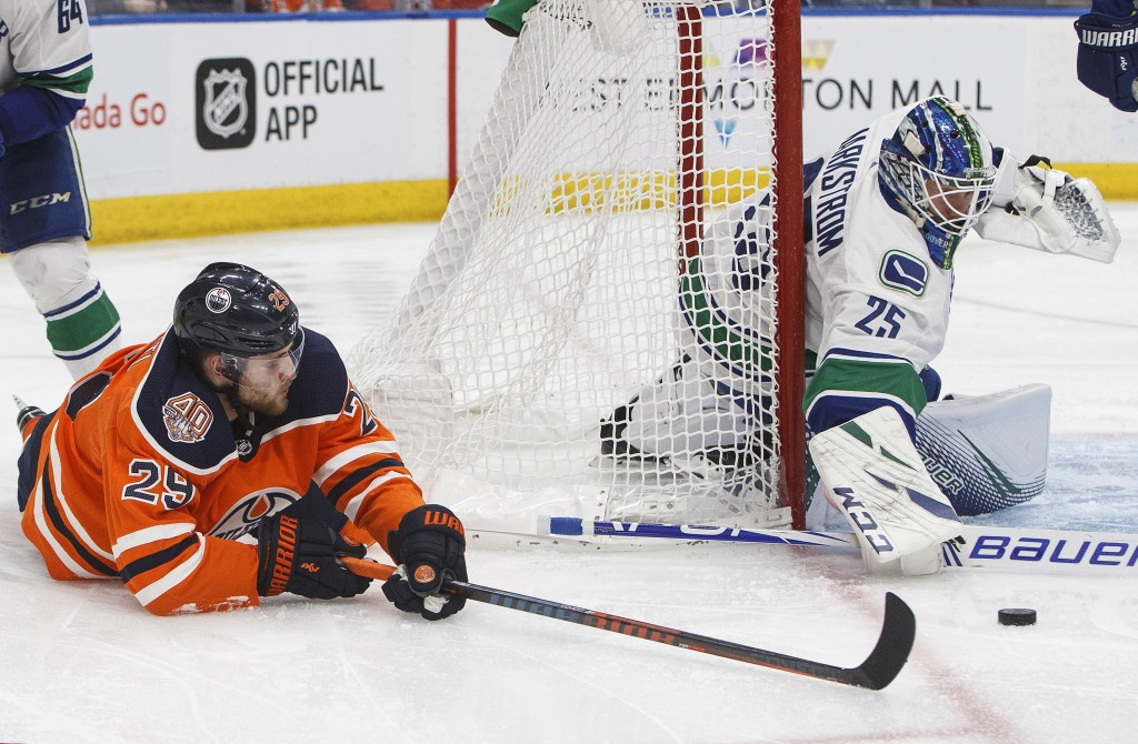 Vancouver Canucks goalie Jacob Markstrom (25) makes a save on Edmonton Oilers' Leon Draisaitl (29) during the second period of an NHL hockey game Thur...