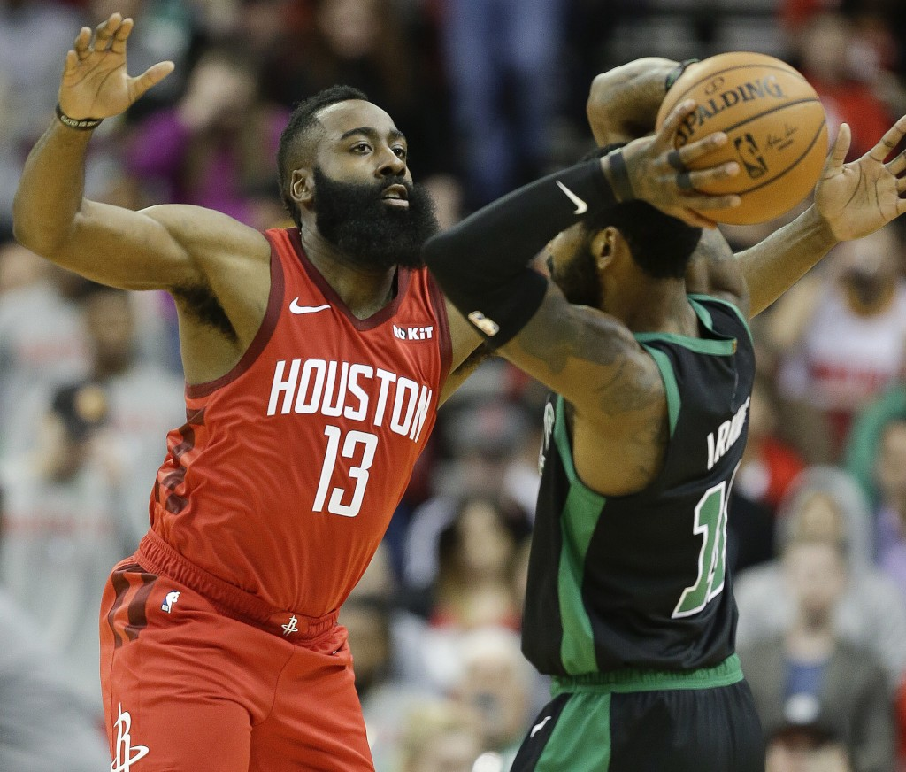 Houston Rockets guard James Harden (13) applies defensive pressure against Boston Celtics guard Kyrie Irving during the first half of an NBA basketbal...