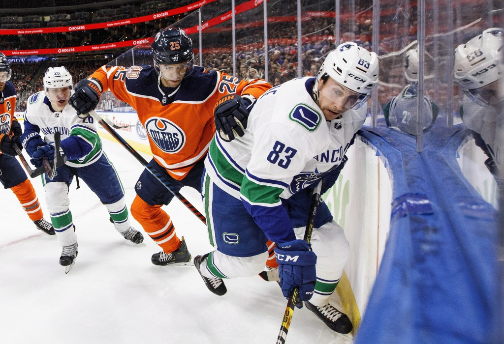 Vancouver Canucks' Jay Beagle (83) and Edmonton Oilers' Darnell Nurse (25) battle for the puck during the first period of an NHL hockey game Thursday,...