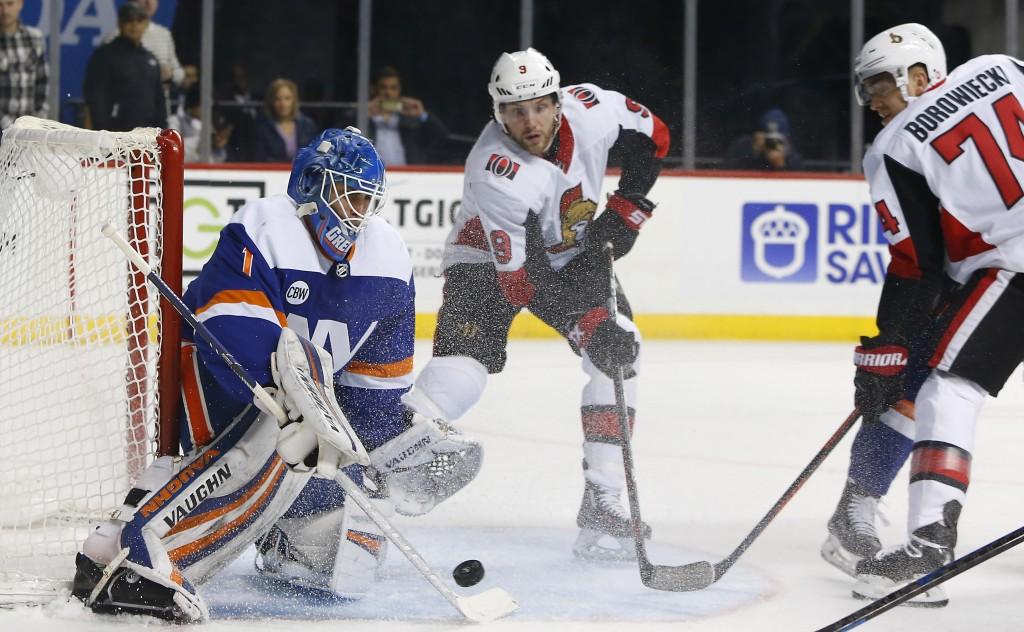 New York Islanders goaltender Thomas Greiss (1) makes a save against Ottawa Senators defenseman Mark Borowiecki (74) during the first period of an NHL...