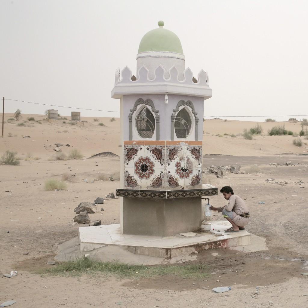 A boy collects water from a fountain on a roadside in Marib, Yemen on July 29, 2018. (AP Photo/Nariman El-Mofty)