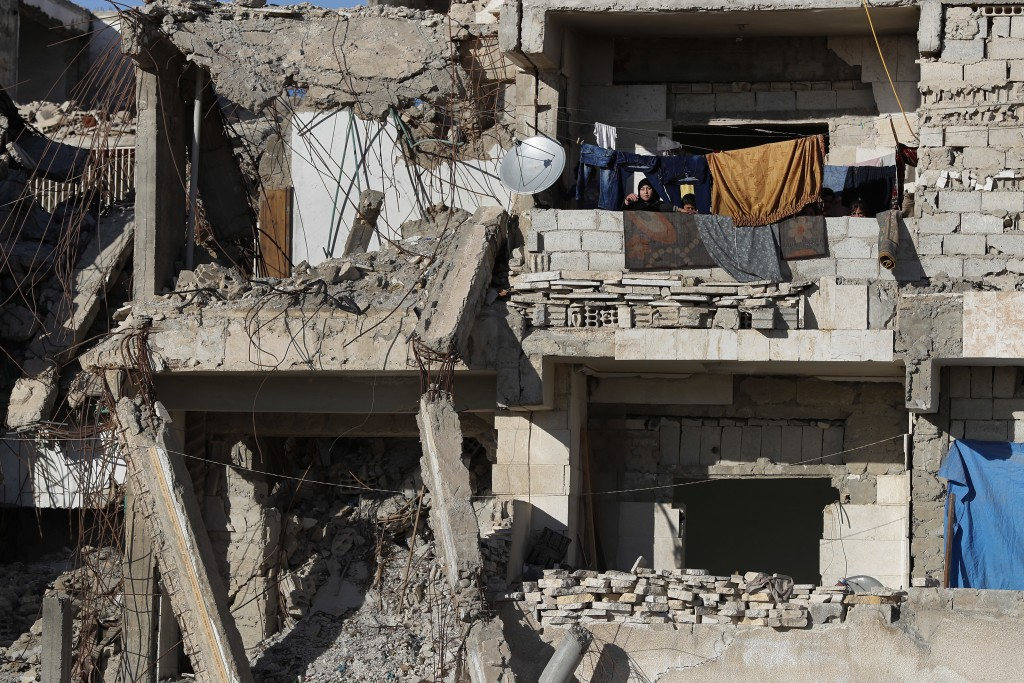 In this March 31, 2018 photo, Syrian kids sit on their balcony apartment that was destroyed during the battle between the U.S.-backed Syrian Democrati...