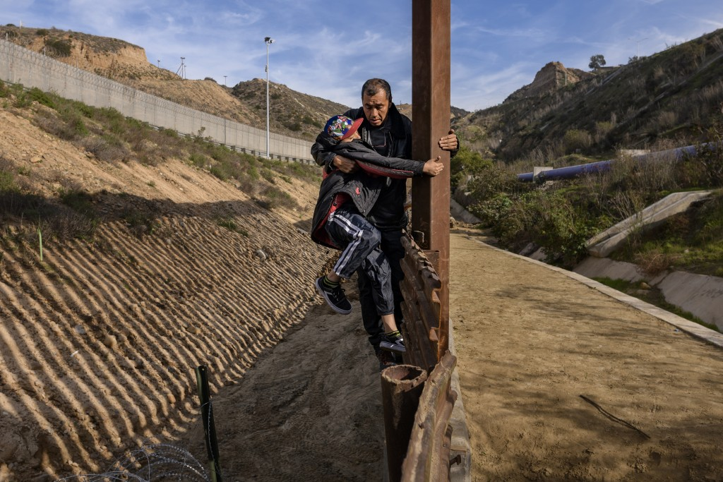 A Honduran migrant grabs his son as they climb the U.S. border fence before jumping into the U.S. to San Diego, Calif., from Tijuana, Mexico, Saturday...